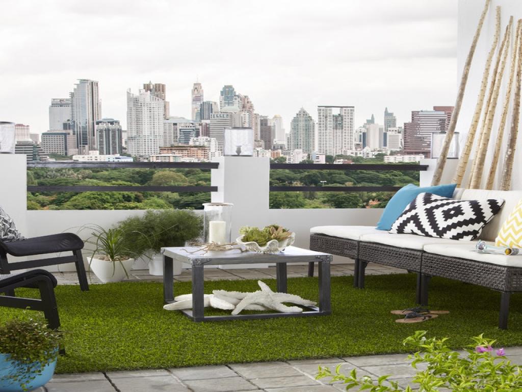 Dekorasi balkon apartemen dengan rumput sintetis dan bantal cushion kecil